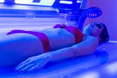 Woman in bikini tanning in wellness spa solarium