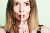 picture of hush  - Portrait of young woman. Girl asking for silence or secrecy with finger on lips hush hand gesture on green