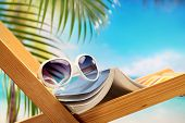 stock photo of palm-reading  - Summer holiday setting with book on beach chair - JPG