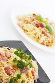 Spaghetti carbonara with fried bacon in two plates on white background