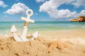 Anchor with starfish on a sandy beach - summer holiday concept