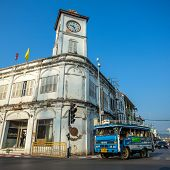 PHUKET TOWN, THAILAND - March 3: A songthaew, local bus passing by the Promthep Clock Tower on March
