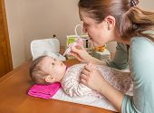 Mother cleaning mucus of baby with nasal aspirator