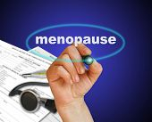 stock photo of ovulation  - writing word MENOPAUSE with marker on gradient background - JPG