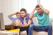 friendship, sports and entertainment concept - sad male friends with vuvuzela watching sports on tv at home