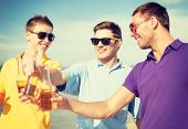 summer, holidays, vacation and happy people concept - group of friends having fun on the beach with