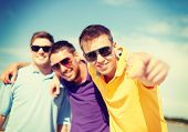 summer, holidays, vacation and happiness concept - group of friends having fun on the beach and poin