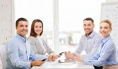 business, technology and office concept - smiling business team with smartphones having meeting in office