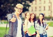 summer holidays, education, campus and teenage concept - smiling male student in black eyeglasses with group in the back showing thumbs up