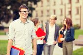 summer holidays, education, campus and teenage concept - smiling teenage boy in eyeglasses with clas