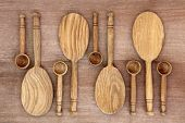 Rustic wooden kitchen spoons over old papyrus grunge background.
