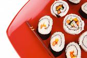 Maki Sushi : Maki Rolls and California rolls made of fresh raw Salmon, Tuna and Eel . on red dish wi