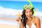 Beach travel woman with snorkel and starfish on vacation in bikini enjoying summer vacation holidays on tropical resort by ocean sea. Beautiful young mixed race Asian Caucasian woman smiling happy.