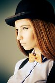 Elegant girl model poses in blouse, bow tie and bowler hat. Refined style of old Europe. Sepia.