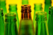 Ten empty beer bottles on a yellow background
