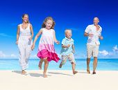 Family having fun on a beach. Young family enjoying their summer vacation.