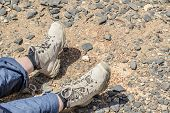 stock photo of tramp  - Closeup of tramping boots of a resting person on Jebel Shams Oman - JPG