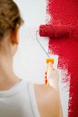 Young woman painting a room with red color