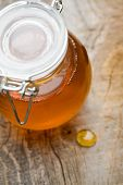 Liquid honey in small glass jar, selective focus
