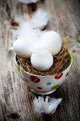 White easter eggs in cup with feathers