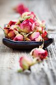 Dried rose buds on wooden table, selective focus