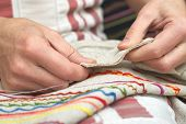 foto of thread-making  - Woman hands sewing with needle and thread  - JPG