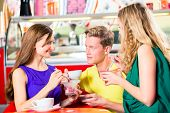 Friends meeting in ice cream parlor or cafe with cappuccino and ice-cream