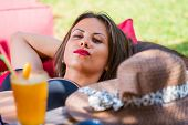Pretty woman relaxing outdoors at summer lounge