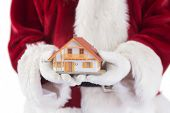 Santa holds a tiny house in his hands on white background