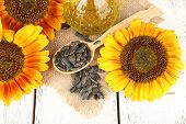 Sunflowers with oil and seeds on wooden background