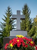 Black granite tombstone cross and red and yellow floral tribute