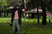 image of longbow  - Beard Man With A Bow And Arrows In The Woods - JPG