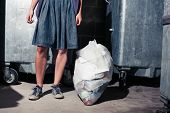 Woman Standing Next To Bins With A Bag Of Rubbish