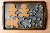 High angle shot of an old baking sheet with holiday gingerbread man cookies and cookie cutters. Horizontal format on wood kitchen table.
