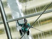 Man At Work Pressure Washing A Glass Roof