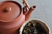 Clay teapot and basket of tea leaves