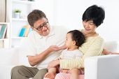 Asian family relaxing indoor, grandparents and grandchild living lifestyle at home.