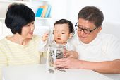 Asian family saving money indoor, grandparents and grandchild living lifestyle at home, financial concept.