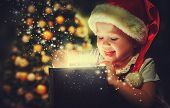 foto of xmas star  - Christmas miracle magic gift box and a child baby girl - JPG