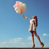 image of legs air  - Fashion girl with  air balloons over blue sky - JPG