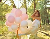 picture of swing  - Young woman is swinging on a swing in summer pine forest - JPG