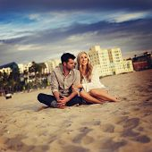 picture of cuddle  - cute couple on beach cuddling while watching sunset - JPG