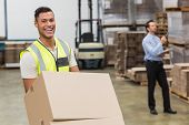 picture of trolley  - Smiling warehouse worker moving boxes on trolley in a large warehouse - JPG