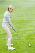 picture of ladies golf  - Lady golfer on the putting green on a foggy day at the golf course - JPG