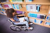 pic of disability  - Smiling disabled student in library reading book at the university - JPG