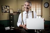 foto of 1950s  - Cheerful businessman showing a blank sign and smiling 1950s office on background.