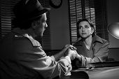 picture of office romance  - Handsome supportive detective at office desk holding a young woman - JPG