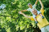 foto of grandparent child  - happy grandfather and child have fun and play in park on beautiful  sunny day - JPG