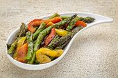 picture of teardrop  - roasted asparagus salad with bell pepper on a teardrop shaped bowl against white painted rustic wood - JPG