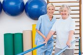 pic of physical therapist  - Senior woman and therapist smiling at camera in fitness studio - JPG